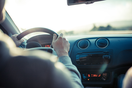 Man driving car, hand on steering wheel, looking at the road ahead.